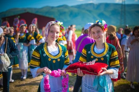 Bulgarian girls dressed in traditional folklore costumes holding roses and a crown during the Rose Festival in Bulgaria