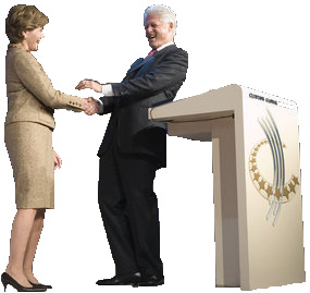 Bill Clinton shaking hands with Laura Bush at the podium