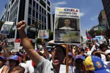 """Opposition supporters shout during a rally against Venezuela's President Nicolas Maduro's government and in support of the political leaders in prison, in Caracas May 30, 2015. The banner with pictures of jailed political leaders Leopoldo Lopez and Daniel Ceballos reads, """"Venezuela in solidarity with Leopoldo and Ceballos"""". The two opposition leaders were jailed a year ago for their roles in deadly protests against the government of socialist President Nicolas Maduro. REUTERS/Carlos Garcia Rawlins"""