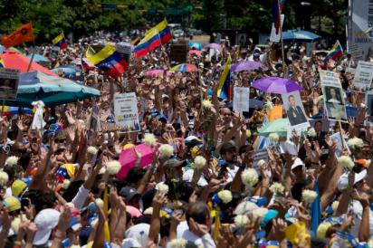Opposition demonstrators hold up white flowers and pictures of political prisoners as they protest the government in Caracas, Venezuela, Saturday, May 30, 2015. Venezuelans gathered across the country to voice their anger with the administration and demand a firm date for this year's legislative elections. (AP Photo/Fernando Llano)