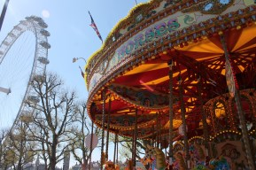 A colorful carousel painted the canvas along a plain-white London Eye.