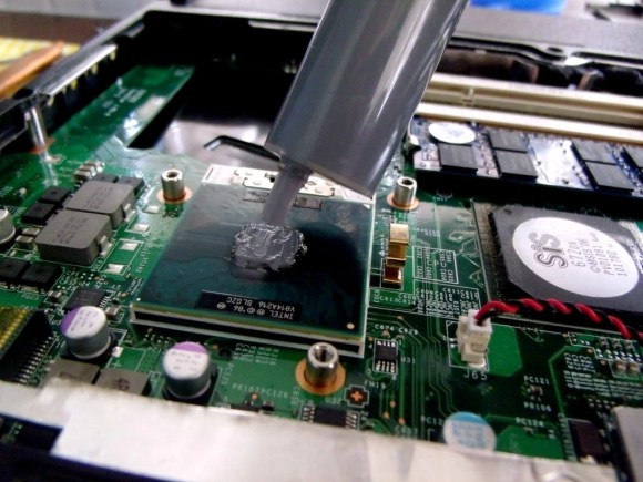 Applying thermal paste on a gaming laptop's processor.
