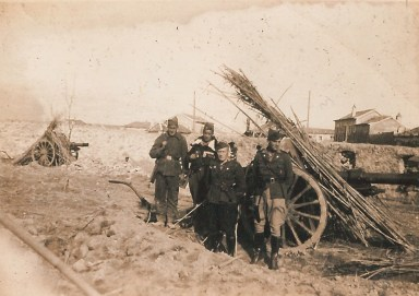black-and-white picture of a group of Irish Brigade volunteers in military uniforms, posing in front of two cannons