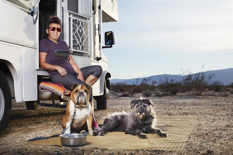 Portrait of mid adult woman and two dogs sitting on camper van step, Borrego Springs, California, USA