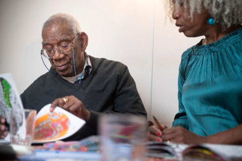 91-year-old man coloring at home with his 62-year-old daughter