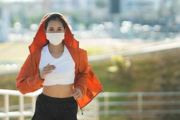 Woman runners morning exercise she wears a nose mask. Protection against dust and viruses. Coronavirus COVID-19
