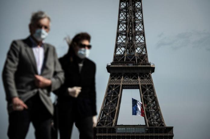 A man and a woman wearing facial masks walk on the Place du Trocadéro in Paris on May 11, 2020.
