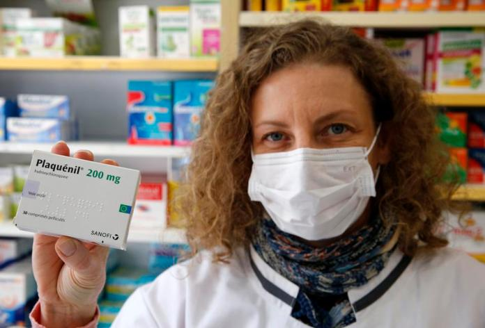 A pharmacy employee with a box of Plaquenil (Hydroxychloroquine) on March 27, 2020 in Paris, France.
