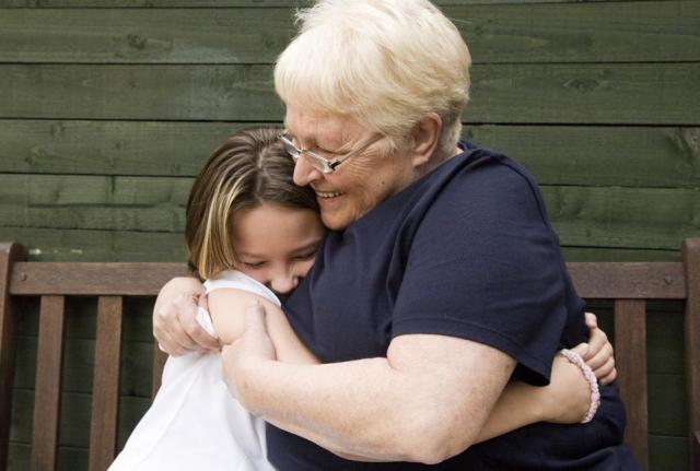 Senior woman hugging granddaughter on bench outdoors