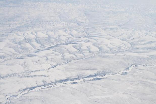 Snow-capped mountains of Verkhoyansk covered in snow Olenyok River Aerial Northern Siberia Russia