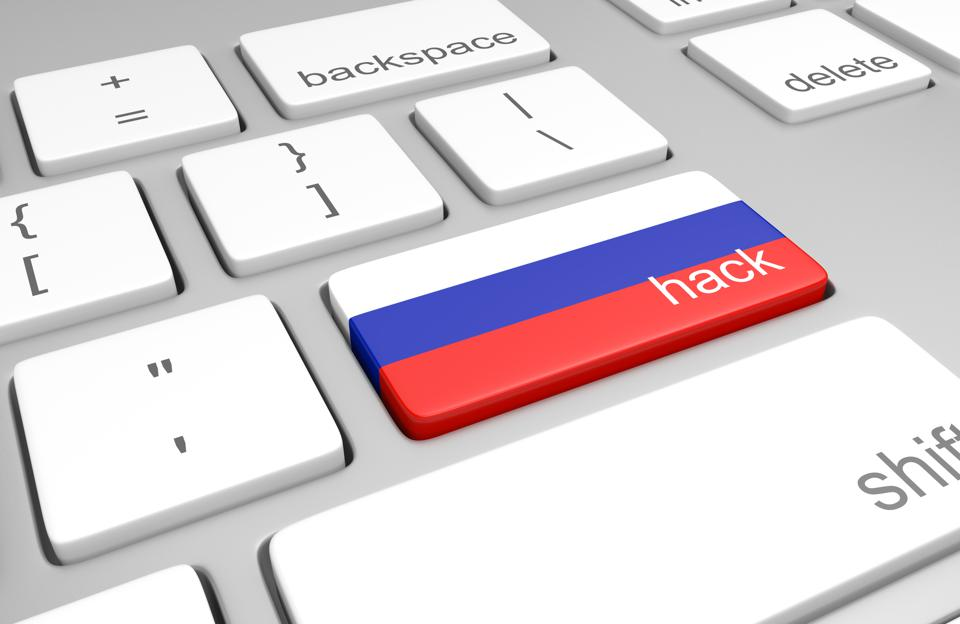Closeup of keys on a computer keyboard, with one bearing the Russian flag colors and a label for hacking.