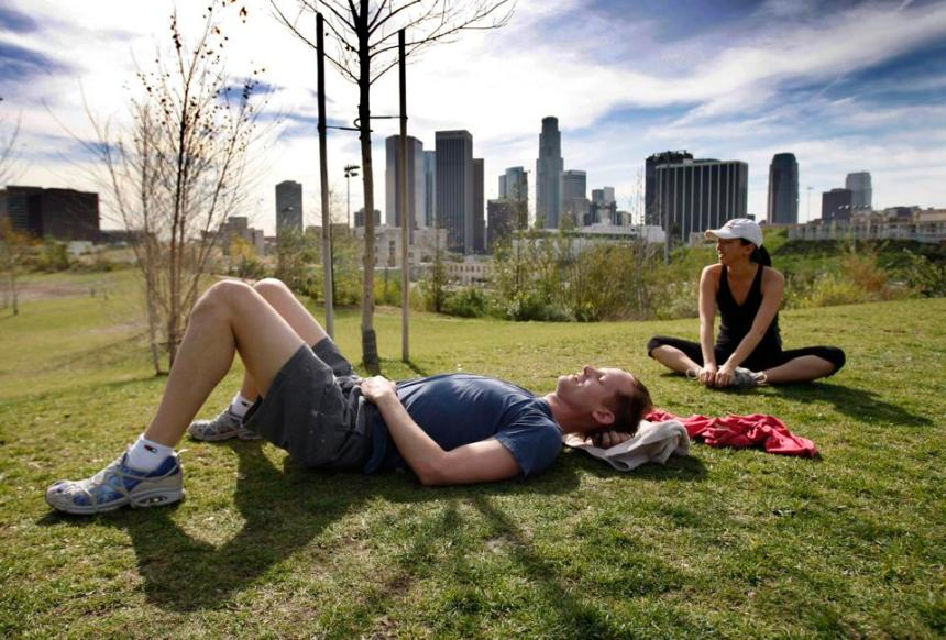 Joy Osmanski and Corey Brill, of Los Angeles, take advantage of warm weather to rest while exercisi