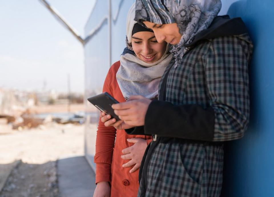 Two Syrian refugees use a mobile phone at the Za'atari camp in Jordan. With the launch of its new Cryptofund, UNICEF aims to build institutional knowledge and prepare for a digitally financed future.