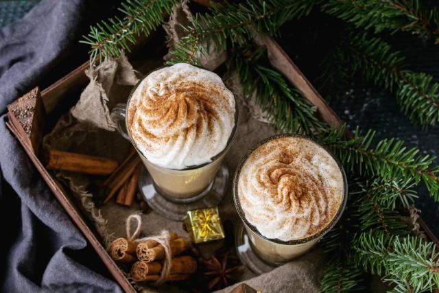 Pumpkin spicy latte with whipped cream and cinnamon in two glasses standing in wooden board with textile and Christmas decoration and fir tree other dark background. Christmas theme, top view