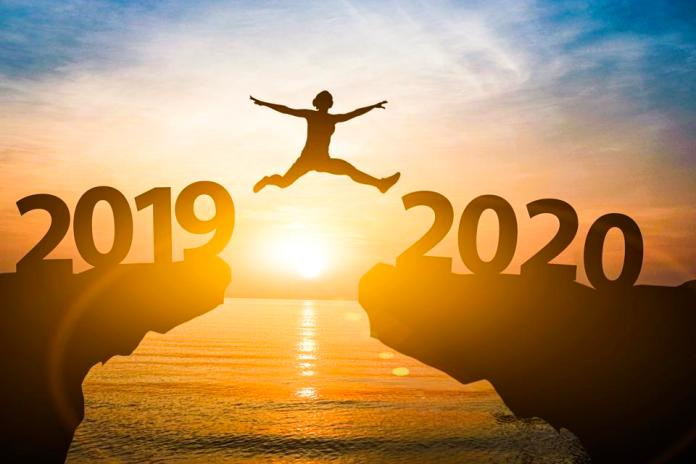 Man jump from year 2019 to 2020. Starting of new year concept.