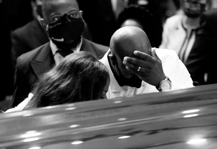 A man holds his head in his hands at a casket.