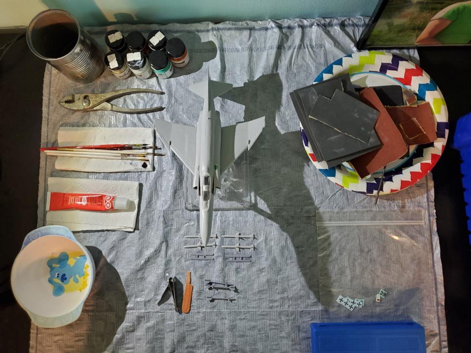 Assembled but still unpainted F-4 Phantom model on neatly organized hobby table.