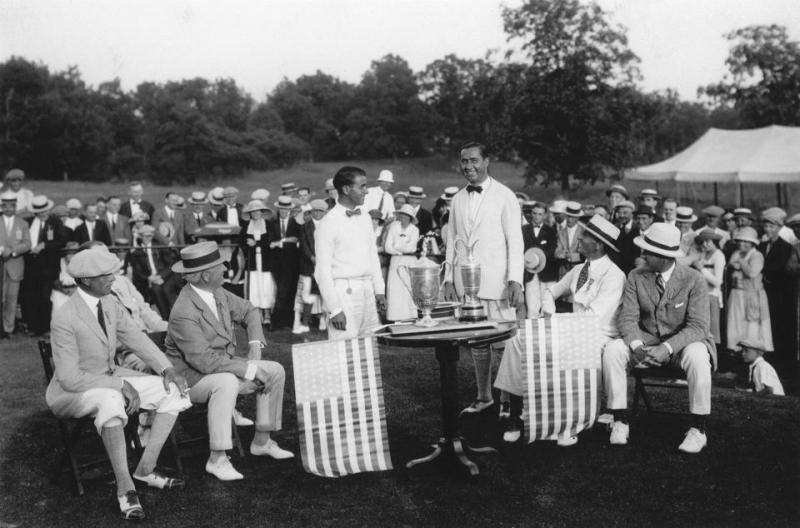 Walter Hagen and Gene Sarazen standing in front of the trophies with a gallery looking out.
