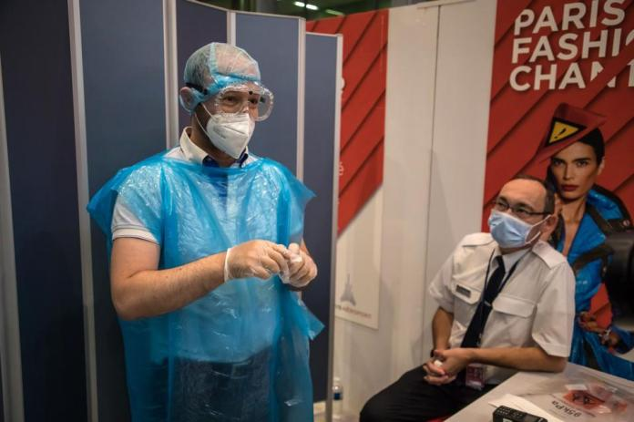 Man in protective suit performs covid-19 tests at Paris Charles de Gaulle airport France