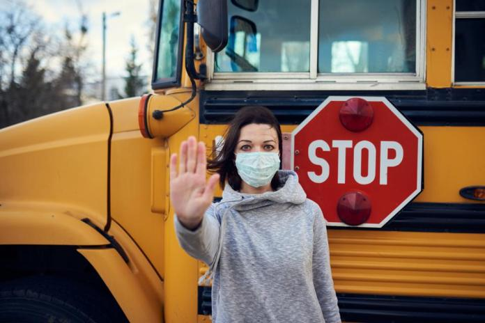 A woman in a protective mask stands on the background of a school bus. Raises a hand and stops the epidemic of coronavirus. A large stop sign is visible on the background.