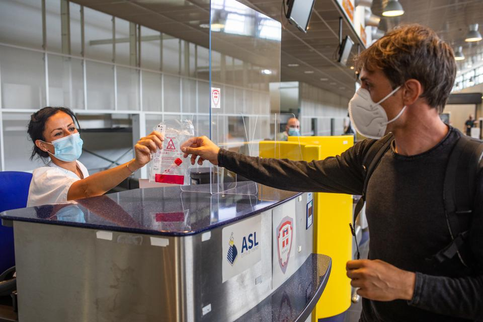 Traveler passes in Covid test at Turin Airport in Italy amid new Covid spike