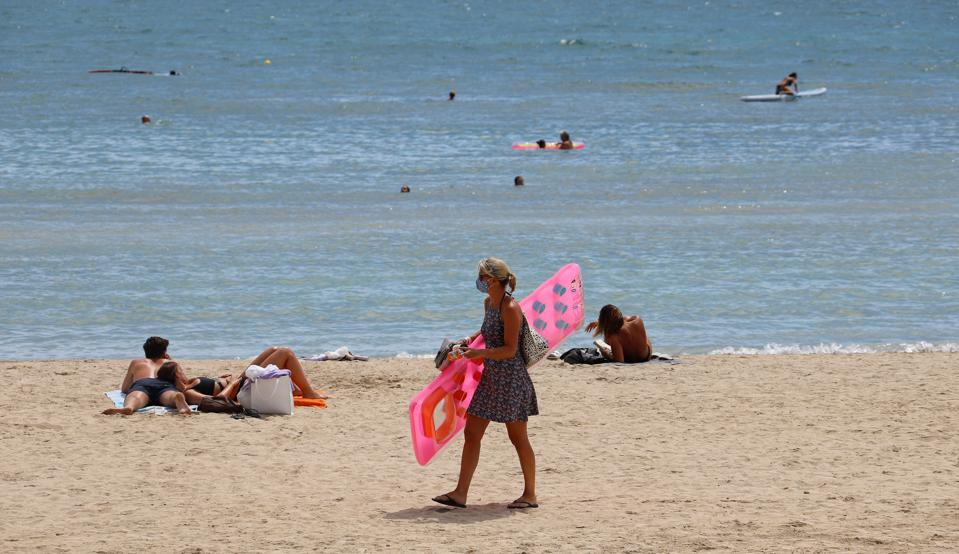 a woman on an empty beach in Mallorca Spain amid new Covid travel bans and quarantines