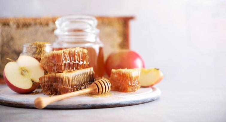 Apples with honey jar, honeycomb on grey background with copy space. Rosh hashanah jewish new year holiday celebration