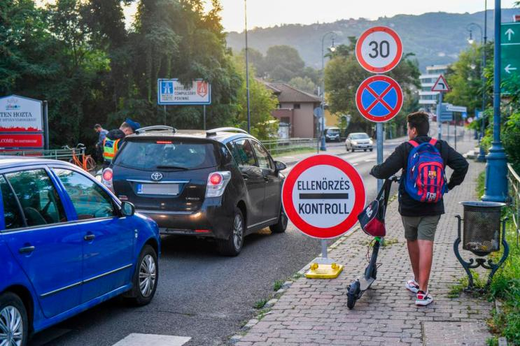 A boy on scooter looks on as Hungarian police officers control drivers at border Europe