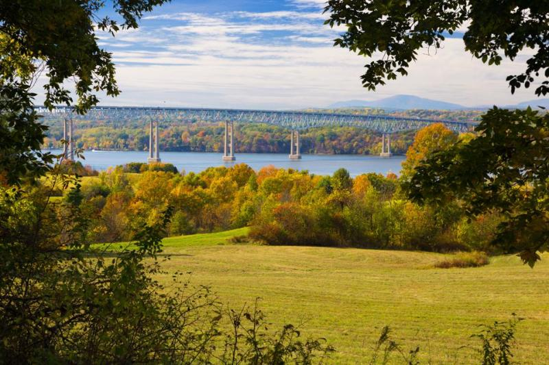 Kingston–Rhinecliff Bridge over Hudson River, Trees in Fall Colors (Foliage) and Blue Sky as seen from Poets' Walk, Red Hook, Hudson Valley, New York.