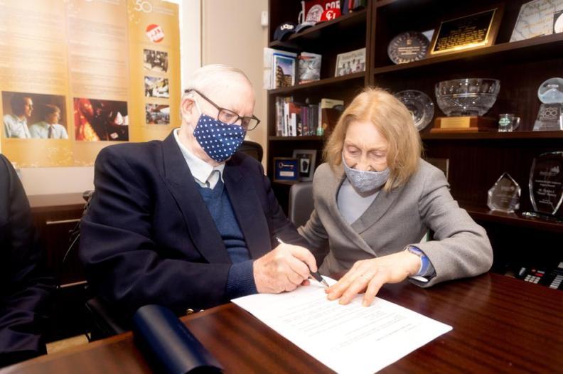 Chuck Feeney signing documents