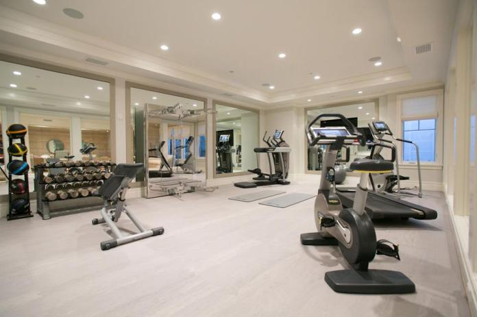 A home gym with light flooring, recessed lighting and white walls.