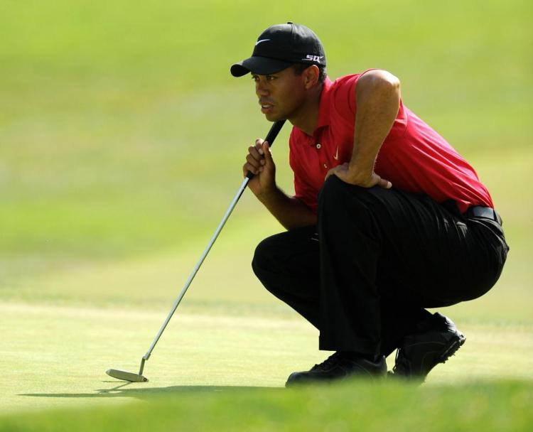 Tiger Woods lines up a putt on the first