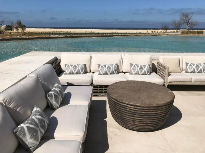 Gray couches next to a large pool, with a beach and ocean in the background