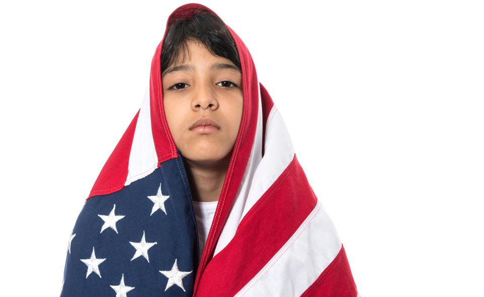 Hispanic little girl wrapped in a U.S. flag.