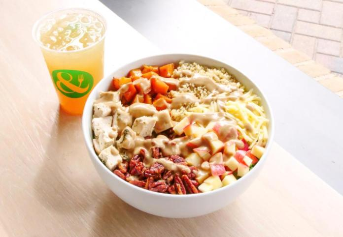 A bowl of healthy proteins sits on a table alongside an aqua fresca