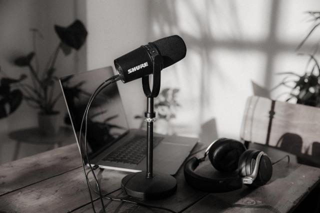 Shure SM7V on a mic desk stand with a pair of headphones and a laptop