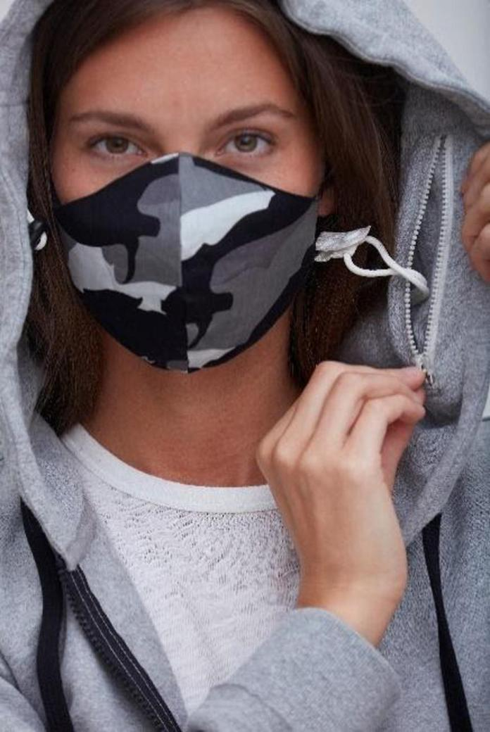Woman wearing hoodie and mask.