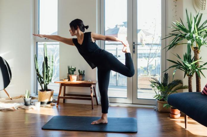 Young woman doing yoga exercise at home