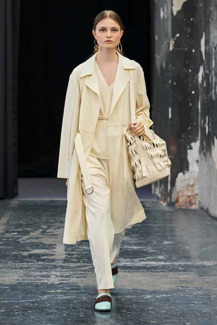 Duster with belt effect, underneath v-neck shirt combined with soft lined trousers. The look is in bi-stretch wool crepe. Nappa belt with double knotted tubular and on the shoulder bucket bag in cow leather.