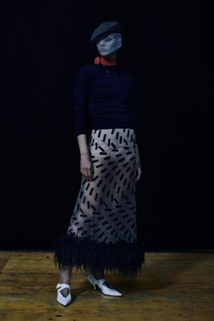 Navy knit circular cut jumper worn with a cream tulle skirt with black tape print with a purpose and black farmed plumed trims, and cream knitted knickers. Cream chiffon ghillies and white leather Tango pumps