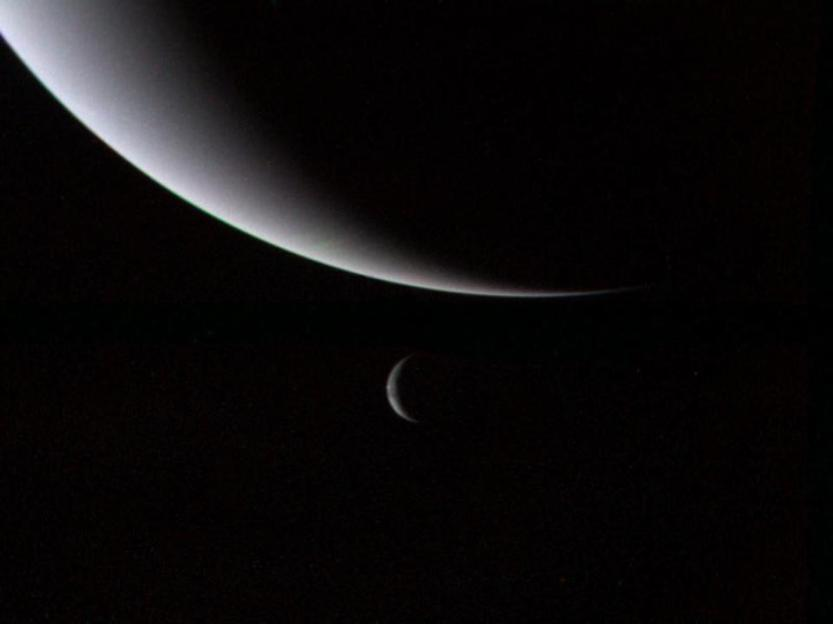The illuminated crescents of Neptune (foreground) & its largest moon Triton (background).