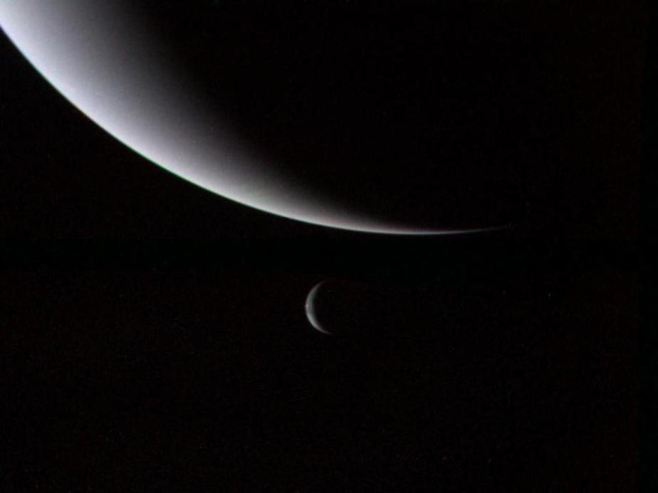 The illuminated crescents of Neptune (foreground) & its largest moon Triton (background).
