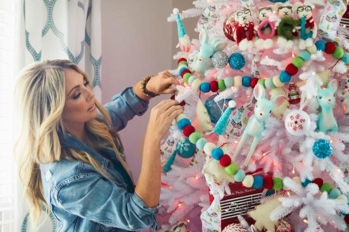 Jenny Reimold decorates a white Christmas tree with ornaments