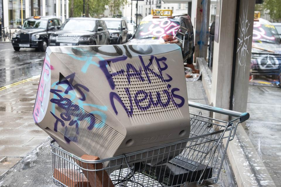 A television at a shopping trolley with the words Fake...
