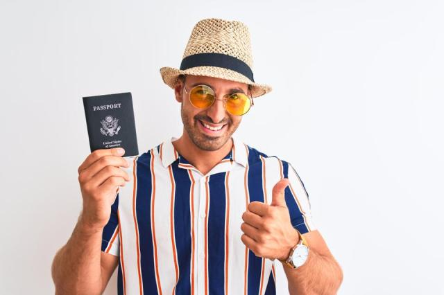Young tourtist man wearing summer hat and holding USA passport over isolated background happy with big smile doing ok sign, thumb up with fingers, excellent sign
