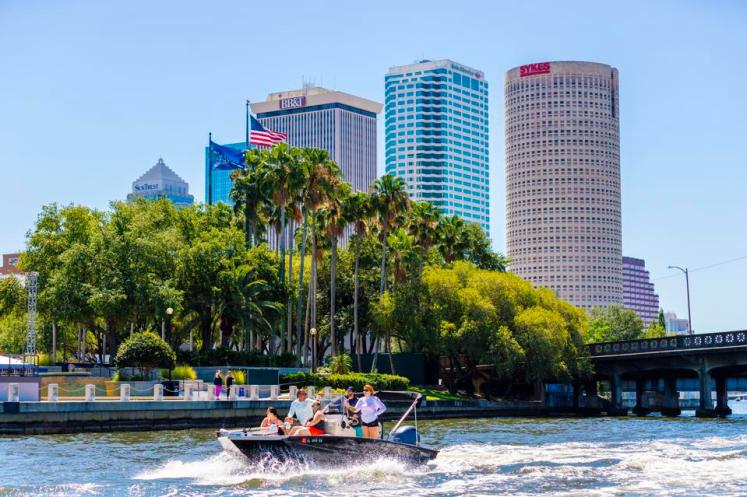 People boating on a river in front of the Tampa skyline