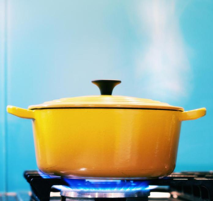 Yellow lidded pot steaming on lit gas stove