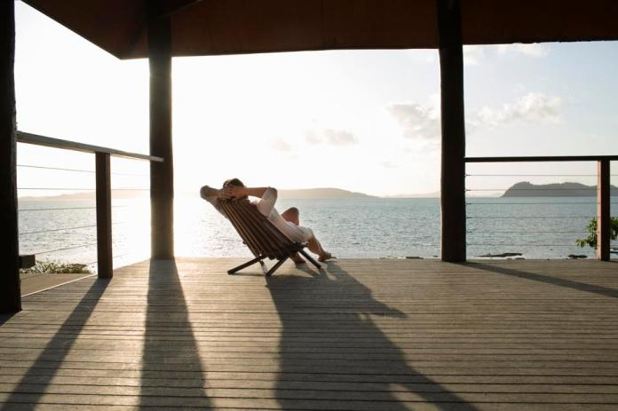 Woman relaxing in deck chair on veranda.