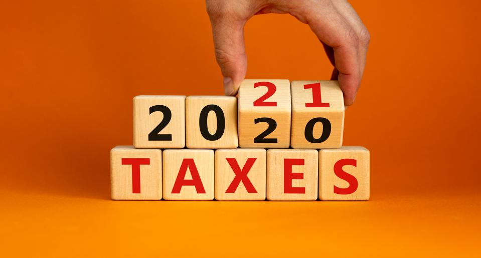 Business concept of planning 2021. Male hand flips wooden cubes and changes the inscription 'Taxes 2020' to 'Taxes 2021'. Beautiful orange background, copy space.