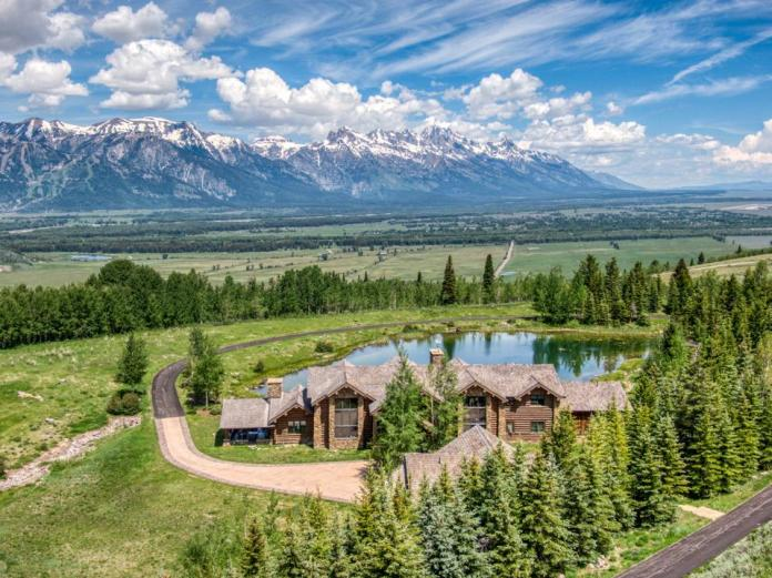 A rustic home in front of a mountain range.